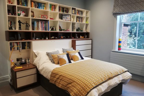 Bed surrounded by shelves and drawers